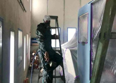 One of the spray painting technicians respraying sections of a crane