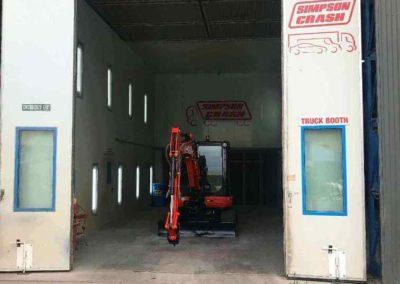 A trench digging machine in a spray booth after being spray painted and then baked in the oven